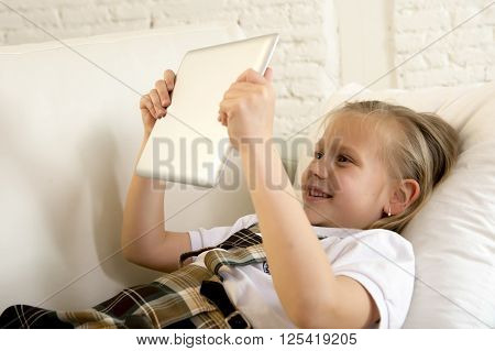 sweet cute and beautiful 6 or 7 years female child with blond hair in school uniform lying on home sofa couch using internet app on digital tablet pad playing online game smiling happy