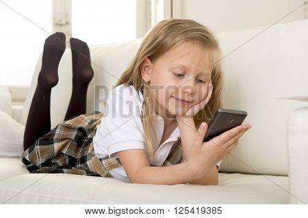young sweet cute and beautiful 6 or 7 years blond old girl in school uniform lying on home sofa couch using internet app on mobile phone playing online game looking happy and relaxed