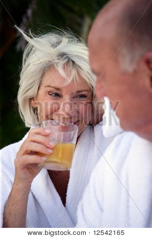 Portrait of a smiling senior woman drinking a glass of orange juice