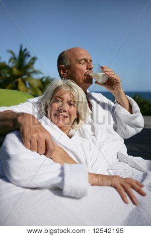 Portrait of a smiling senior woman and a senior man drinking a glass of water