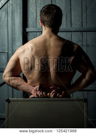 Young man with naked torso with valise