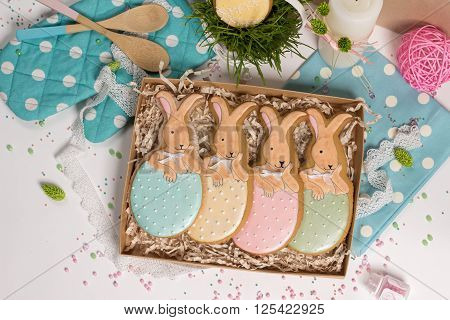family holiday present box with nice sweet multicolored trendy easter rabbits honey-cake on kithen table with a lot of beautiful details food photo