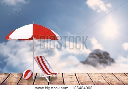 Image of sun lounger and sunshade against mountain peak through the clouds