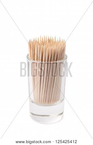 Glass shot filled with the wooden toothpicks isolated over the white background