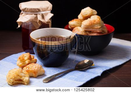 Cup of tea home-made cookies and jar of jam. On a napkin from fabric a dark background a close up