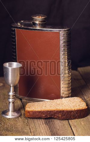 Flask shot glass and bread on a wooden table. The shot glass is turned from steel a table from old gray boards rye bread a dark background