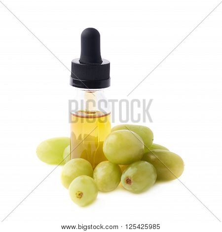 Grape seed oil essence in a small bottle with a pipette, surrounded with the multiple white table grapes, composition isolated over the white background
