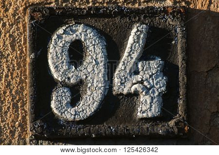 Old retro weathered cast iron plate with number 94