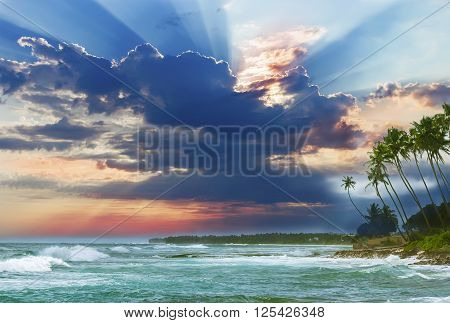 Beautiful sunrise tropical beach white sand turquoise ocean water . Palm trees and tropical vegetation on the coast.
