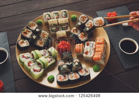 Japanese food restaurant, sushi maki gunkan roll plate or platter set. Hand take roll. Set for two with chopsticks, ginger, soy, wasabi. Sushi at rustic wood background and black stone. POV at black.