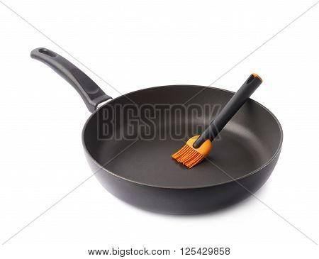 Silicone oil brush in a black frying pan, composition isolated over the white background