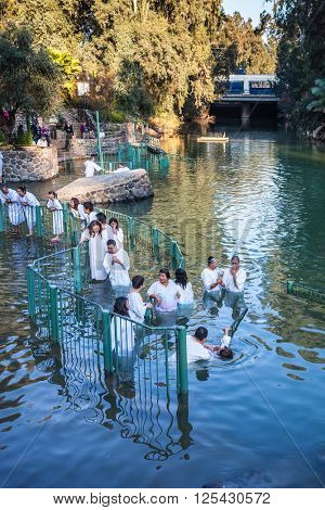 YARDENIT, ISRAEL - JANUARY 21, 2012: Christian pilgrims enter Jordan River waters. They make  baptism ceremony in honor of Jesus Christ's baptism here