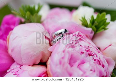 Golden wedding rings with diamonds lie inside peony flower in bridal bouquet. Symbol of love and marriage. Wedding bouquet. Bride's traditional symbolic accessory. Floral composition with peony flowers.