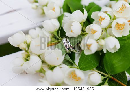 Golden wedding rings with diamonds lie inside jasmine (Philadelphus) flower in bridal bouquet. Symbol of love and marriage. Wedding bouquet. Bride's traditional symbolic accessory. Floral composition with jasmine flowers.