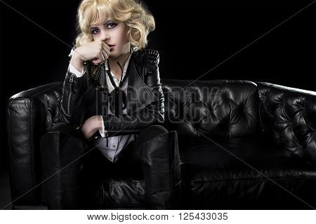 Female in black leather and shades posing arrogantly like a famous rockstar