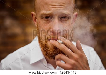 portrait of smoking young red hair man with beard horizontal