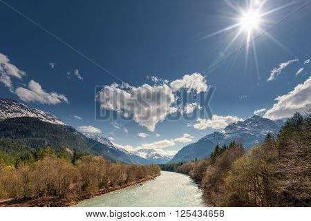 sun over rural river between mountains at spring