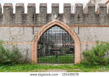 arched entrance of a medieval castle closed by an iron grille gate.