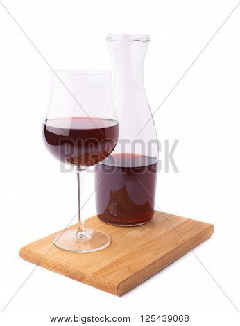 Red wine glass and bottle composition over the wooden serving board, isolated over the white background