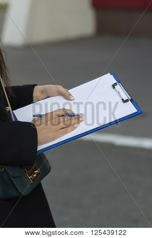 girl with French manicure keeps clip board