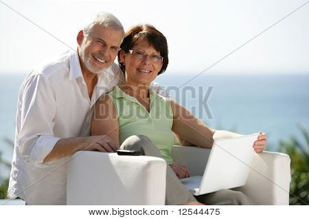 Portrait of a senior couple smiling with a laptop