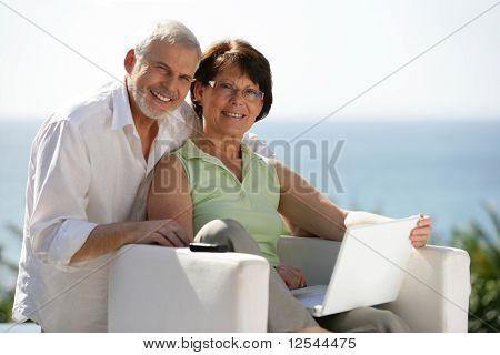 Portrait of a senior couple smiling with a laptop