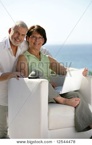 Portrait of a senior Couple lächelnd mit einem laptop