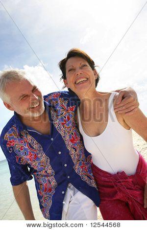 Portrait of a lächelnd senior Couple walking on the beach