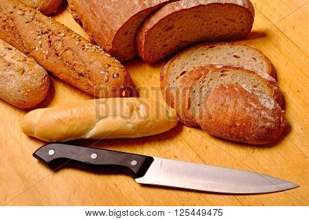 lot of bakery goods with knife on wooden board