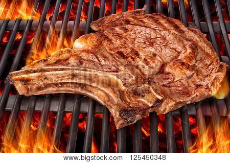 Cooking t bone steak on barbecue grill. Close up.