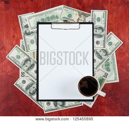 Blank paper sheet in clipboard placed on center of money dollar and wood background, coffee cup, business concept and information mockup
