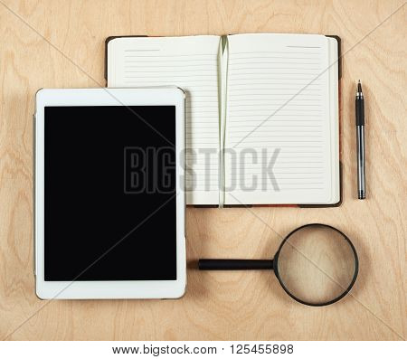 Flat lay of tablet computer, notebook, coffee cup  and pencil with blank center on wood background, top view