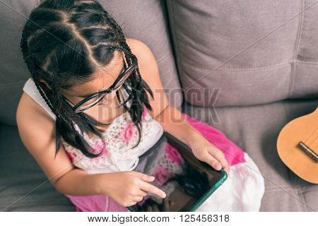 Cute Little Girl,playing With Computer At Home Laying On Sofa