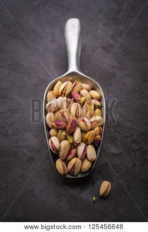 Pistachios in a scoop closeup. Pistachios over dark background
