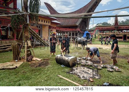 Men Impose Buffalo Meat From Cauldron At The Funeral Ceremony In Tana Toraja