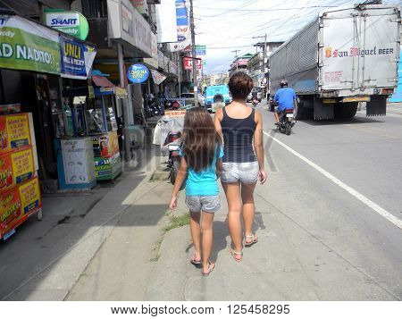 MAASIN, SOUTHERN LEYTE, PHILIPPINES / AUGUST 2, 2011: Two girls walk through the busy streets of downtown Maasin in Southern Leyte.