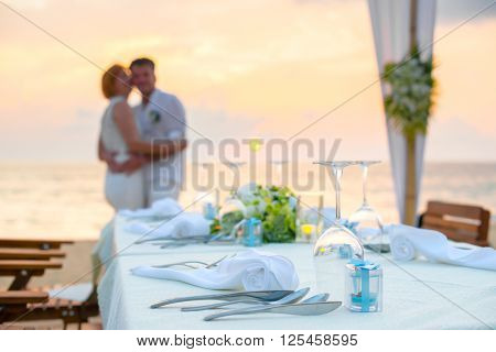 Romantic dinner setting on the beach at sunset with couples background