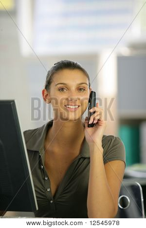 Portrait of a young woman phoning in front of a laptop computer