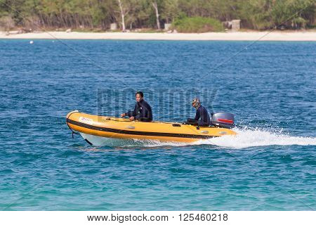 Chonburi Thailand - April 9 2016: Two security guards riding the orange plastic speedy boat of Samae San island the preserved area for nature of Suttahip in Chonburi Thailand.