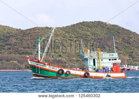 Chonburi Thailand - April 9 2016: Wooden fishing boat with sailors arrived the beach after fishing for seafood in area of Suttahip the Gulf of Thailand.
