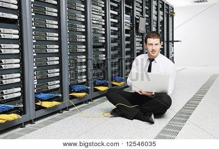 Empresário com Laptop na sala de servidores de rede