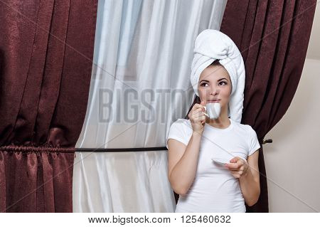 Young girl drinking morning coffee after a shower. Girl dressed in a white t-shirt. Towel on the head. Morning fees.