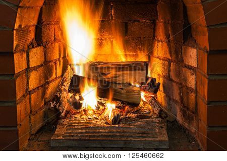 Burning Wood In Brick Fireplace