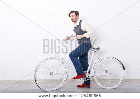Young romantic man in the vest. Men's fashion. Man is going to ride a bike.