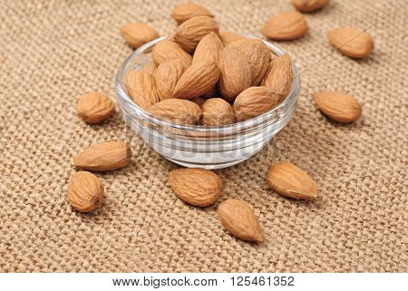 Dried almonds on glass bowl on background