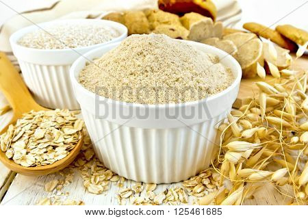 Flour Oat In White Bowl With Flakes In Spoon On Board