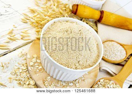 Flour Oat In White Bowl With Flakes On Light Board