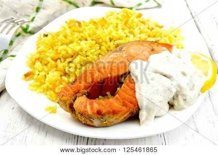 Pink salmon with lemon milk sauce and rice with turmeric in a dish a towel and a fork on the background of wooden boards