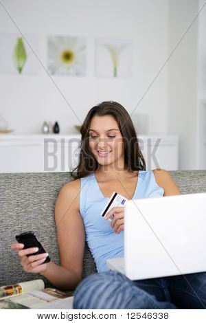 Portrait of a young woman making an online purchase with a laptop computer and a phone