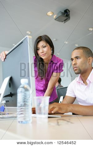 Portrait of a young woman and a young man in front of a desktop computer